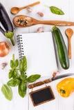 Ingredienser och kök bearbetar på vitbakgrund Receptbok och ingredienser för att laga mat vegetab Arkivbilder