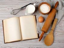 Ingredienser och kökhjälpmedel med det gamla tomma receptet bokar Arkivbild
