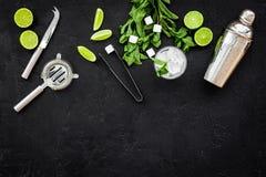 Ingredienser och lerkärl för framställning av mojito Skivor av limefrukt, mintkaramell, sockerkuber, exponeringsglas med iskuber, arkivfoto