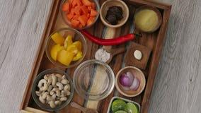 Ingredienser tj?nade som p? magasinet som var klart att laga mat gr?nsaks?s fr?n mor?tter, kasjuer, gul spansk peppar, misodeg arkivfilmer