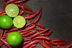 Ingredienslimefrukter och chili på mörkt trä Royaltyfri Fotografi