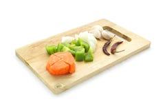 Ingrediensuppsättning av moroten, söt peppar, spansk peppar, capcicum, lök, vitlök, torr chili på det hugga av kvarteret som isol Fotografering för Bildbyråer