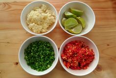 Ingredient of food. Compose of chili, scallion, lime, garlic on the wood background in top view Stock Photos