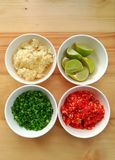 Ingredient of food. Compose of chili, scallion, lime, garlic on the wood background in top view Royalty Free Stock Images