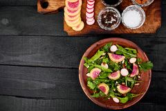 Ingredient and salad brown plate. Mix leaf, Radish, Lettuce, mangold, parsley, dill, arugula, almond, salt, tasty, balsamic pepper Healthy diet Clear food Stock Images