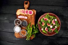 Ingredient and salad brown plate. Mix leaf on wooden cutting board. Radish, Lettuce, mangold, parsley, dill, arugula, almond, salt, tasty, balsamic, pepper Royalty Free Stock Image