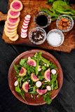 Ingredient and salad brown plate. Mix leaf on wooden cutting board. Radish, Lettuce, mangold, parsley, dill, arugula, almond, salt, tasty, balsamic, pepper Royalty Free Stock Photography