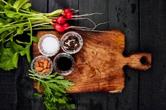 Ingredient for salad. Mix leaf on wooden cutting board. Radish, Lettuce, mangold, parsley, dill, arugula, almond, salt, tasty, balsamic, pepper. Healthy diet Stock Images