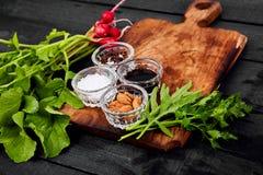 Ingredient for salad. Mix leaf on wooden cutting board. Radish, Lettuce, mangold, parsley, dill, arugula, almond, salt, tasty, balsamic, pepper. Healthy diet Stock Photos