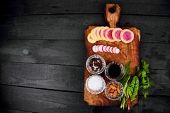 Ingredient for salad. Mix leaf on wooden cutting board. Radish, Lettuce, mangold, parsley, dill, arugula, almond, salt, tasty, balsamic, pepper. Healthy diet Royalty Free Stock Photo