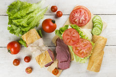 Ingredient for sandwich. Tomatoes, cheese, cucumber, meat, lettuce on a white background Stock Images