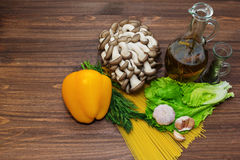 Ingredient for vegeterian pasta dish. Everything is ready for pasta cooking on the table - spaghetti, olove oil with herbs, mushrooms, bell pepper, spices and royalty free stock photography
