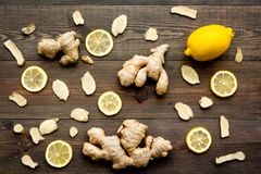 Ingredient for warming tea. Whole and sliced ginger roots, lemon on dark wooden background top view.  Stock Photo