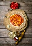 Ζύμη πιτσών με τη σάλτσα ντοματών, τις ντομάτες, και ingrediente την κυλώντας καρφίτσα για την πίτσα Στοκ Εικόνες