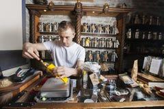 Ingrediente de escavação do proprietário masculino no saco de papel na loja do chá Fotos de Stock