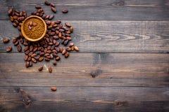 Ingrediente principal para el chocolate Polvo de cacao en cuenco cerca de granos de cacao en espacio de madera oscuro de la copia imagen de archivo libre de regalías