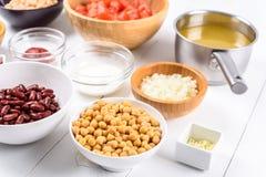 Ingredientes alimentarios blancos y rojos del cebolla y vegetal de la acción de las habas de riñón, de la salsa de tomate, de los Imagen de archivo