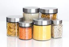 Ingredientes alimentarios en los tarros de cristal, en el fondo blanco Imágenes de archivo libres de regalías