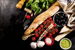 Ingredientes alimentarios italianos apetitosos frescos sabrosos en backgrou oscuro Fotografía de archivo