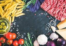 Ingredientes boloñeses de las pastas: penne, carne picadita, tomates, albahaca Fotografía de archivo libre de regalías
