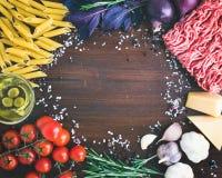 Ingredientes boloñeses de las pastas: penne, carne picadita, tomates, albahaca Foto de archivo libre de regalías