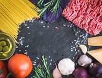 Ingredientes boloñeses de los espaguetis en un fondo de piedra oscuro con Imágenes de archivo libres de regalías