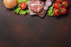 Ingredientes chuleta, tomates, lechuga, bollo, queso, pepinos y cebolla crudos de la hamburguesa en fondo oxidado fotografía de archivo