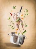 Ingredientes crudos con el pollo entero, verduras, condimento, cuchillo y pote del caldo de pollo que vuelan, del caldo o de la s Fotografía de archivo