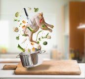 Ingredientes crudos con el pollo entero, verduras, condimento, cuchillo y pote del caldo de pollo que vuelan, del caldo o de la s Foto de archivo