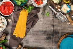Ingredientes crudos para cocinar para las pastas en la tabla de madera fotos de archivo
