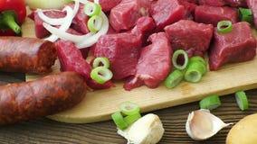 Ingredientes crus para o guisado, a goulash ou a sopa Carne desbastada crua fresca em uma placa de corte de madeira com especiari video estoque