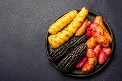 Ingredientes crus peruanos para cozinhar o milho preto e batatas doces Vista superior Fotos de Stock Royalty Free