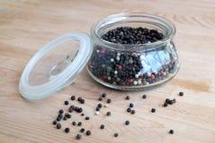 Ingredientes da especiaria quente para o alimento Ainda vida com as sementes da pimenta preta dentro do frasco de vidro redondo e Fotografia de Stock