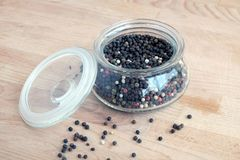 Ingredientes da especiaria quente para o alimento Ainda vida com as sementes da pimenta preta dentro do frasco de vidro redondo e Imagens de Stock