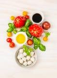 Ingredientes da salada dos tomates da mussarela com folhas da manjericão, óleo e vinagre balsâmico, preparação no fundo de madeir Foto de Stock Royalty Free