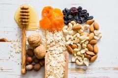 Ingredientes das barras de Granola no fundo de madeira branco imagens de stock
