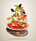 Ingredientes de alimento do mar do voo com massa da pizza, no fundo cinzento Imagens de Stock