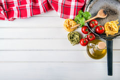 Ingredientes de alimento italianos e mediterrâneos no fundo de madeira Massa dos tomates de cereja, folhas da manjericão e garraf Imagem de Stock Royalty Free