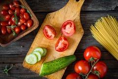 Ingredientes de cocinar frescos en tabla de cortar de madera Tomates y pepinos Fotos de archivo
