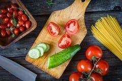 Ingredientes de cocinar frescos en tabla de cortar de madera Tomates y pepinos Foto de archivo libre de regalías
