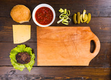 Ingredientes de la hamburguesa con la tabla de cortar de madera Imagen de archivo libre de regalías