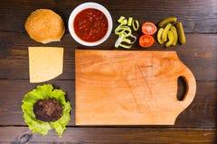 Ingredientes de la hamburguesa con la tabla de cortar de madera Foto de archivo