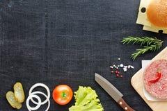 Ingredientes de la hamburguesa en una tabla negra Imágenes de archivo libres de regalías