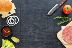 Ingredientes de la hamburguesa en una tabla negra Fotos de archivo libres de regalías