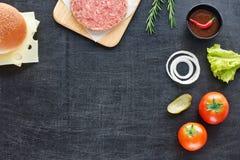 Ingredientes de la hamburguesa en una tabla negra Imagen de archivo libre de regalías