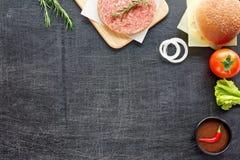 Ingredientes de la hamburguesa en una tabla negra Fotografía de archivo