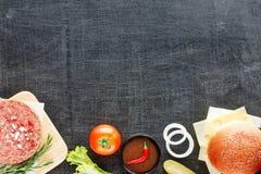 Ingredientes de la hamburguesa en una tabla negra Imagenes de archivo