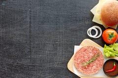 Ingredientes de la hamburguesa en una tabla negra Imagen de archivo
