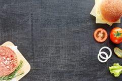 Ingredientes de la hamburguesa en una tabla negra Fotos de archivo
