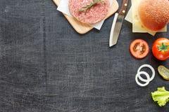 Ingredientes de la hamburguesa en una tabla negra Foto de archivo libre de regalías